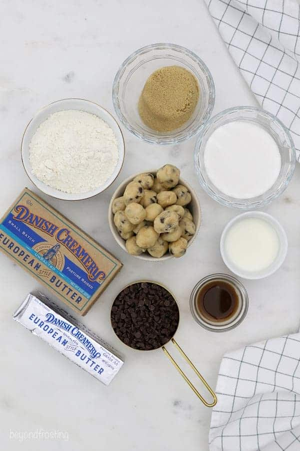 An overhead shot of ingredients in small bowls including sugar, brown sugar, flour, cookie dough, mini chocolate chips and butter