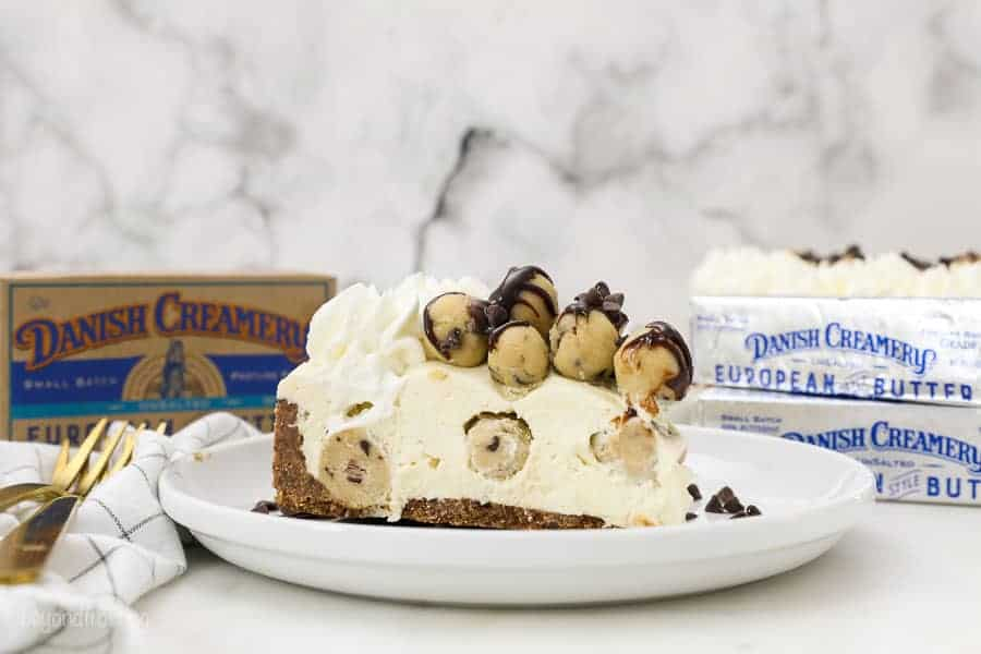 A wide angle shot of a big slice of cookie dough cheesecake with packages of danish creamery butter blurred out in the background
