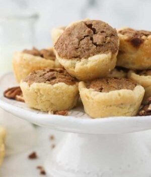 A small white cake stand with mini pecan pies on top
