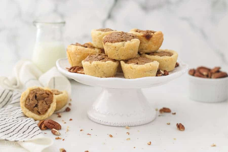 A wide angle shot of pecan tarts on a small white cake stand, with a jar of milk in the background