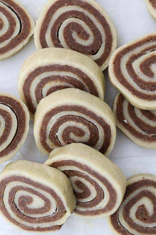 Unbaked Pinwheel Cookies stacked up on parchment paper.