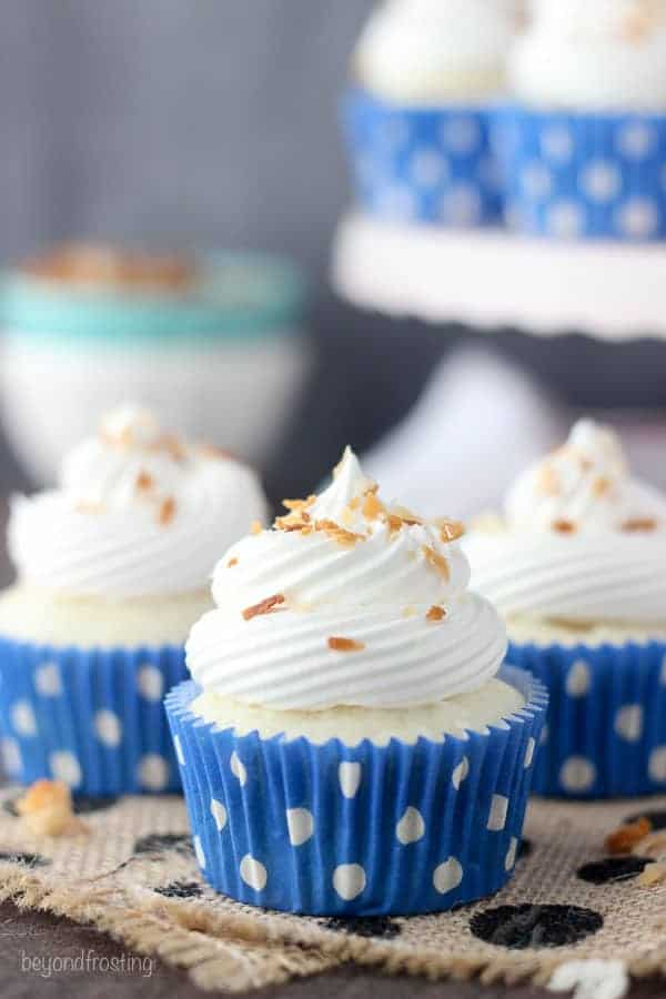 Three pretty cupcakes with bright blue polka dot wrappers and some toasted coconut on top