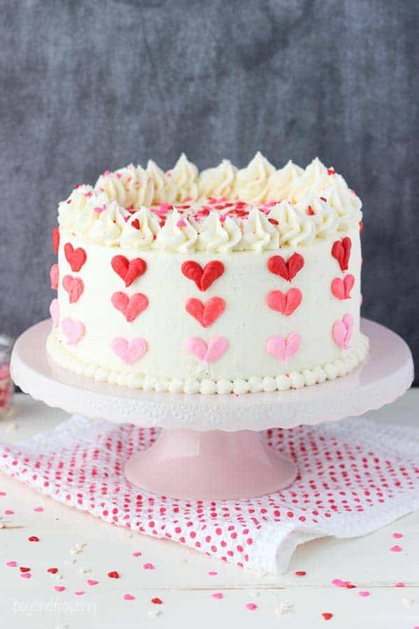 A layer cake with vanilla frosting decorated with 3 shades of red and pink buttercream hearts sitting on a pink cake stand and a red polka dot napkin