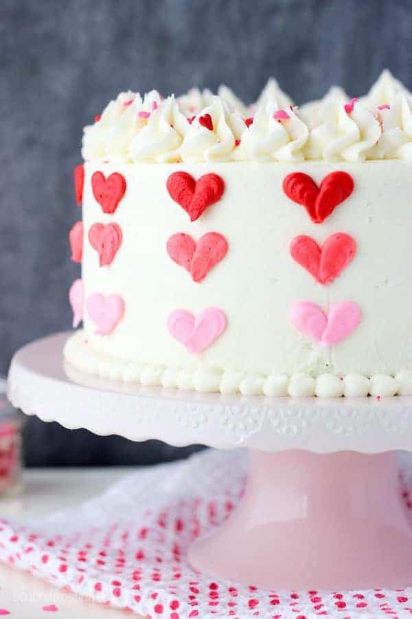 A close up shot of a layer cake with vanilla frosting decorated with 3 shades of red and pink buttercream hearts sitting on a pink cake stand