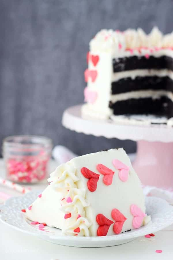 A pretty slice of cake decorated with pink and red buttercream hearts
