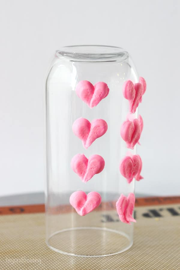 A clear juice glass with pink hearts piped with buttercream frosting
