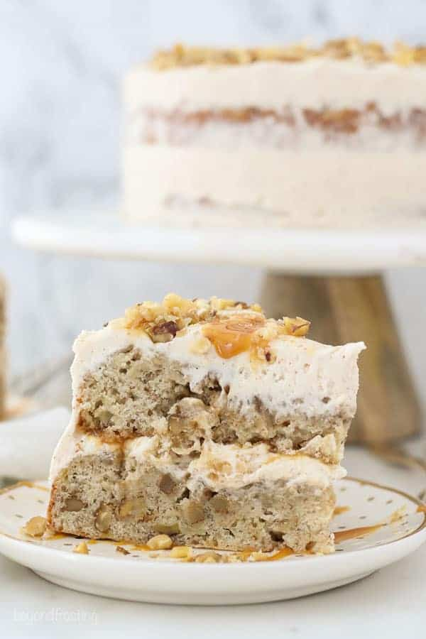 An side view of a slice of banana cake and a cake stand blurred out in the background with frosting and caramel dripping down the side