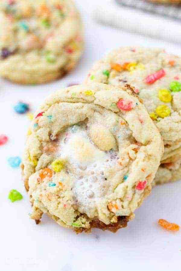A close up of a melted marshmallow on top of a Fruity Pebble cookie leaning up against a stack of cookies