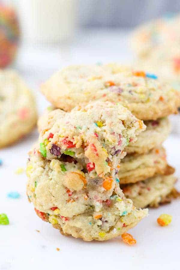 A Fruity Pebble Cookie with a bite missing leaving up against another stack of 4 cookies