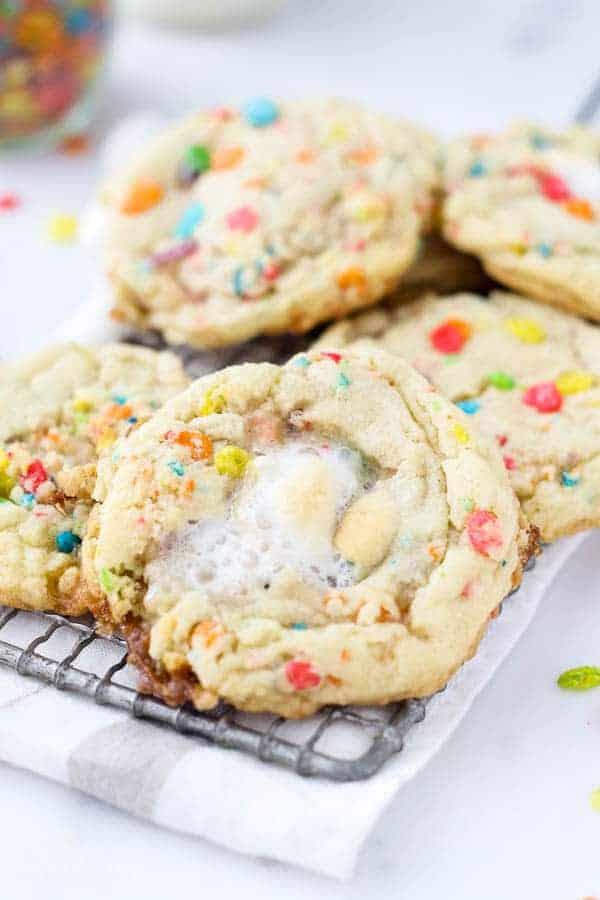 A close up of a melted marshmallow on top of a Fruity Pebble cookie on a vintage wire cooling rack