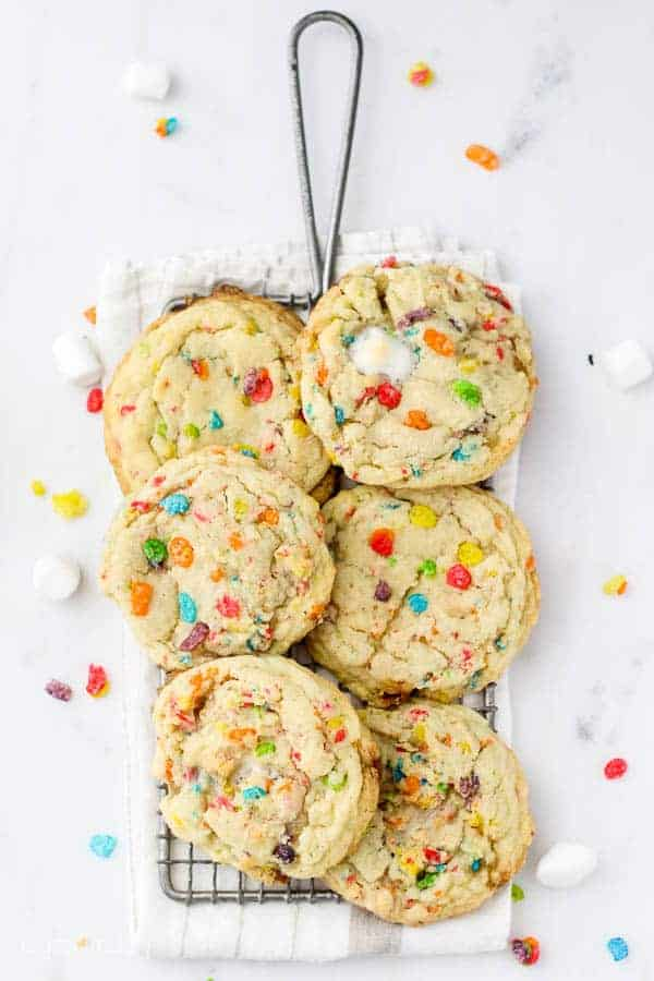 An overhead view of a vintage cooling rack with 6 Fruity Pebble Cookies laid on top