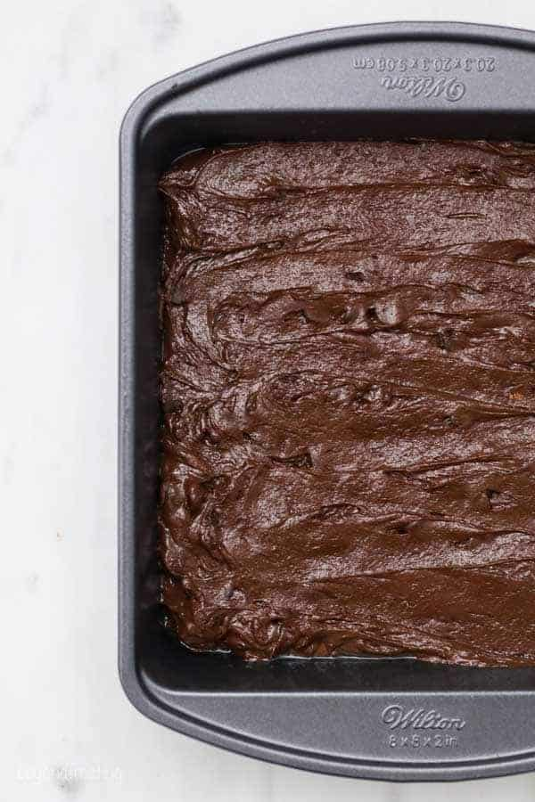 A cropped overhead shot of an 8-inch brownie pan filled with brownie mix