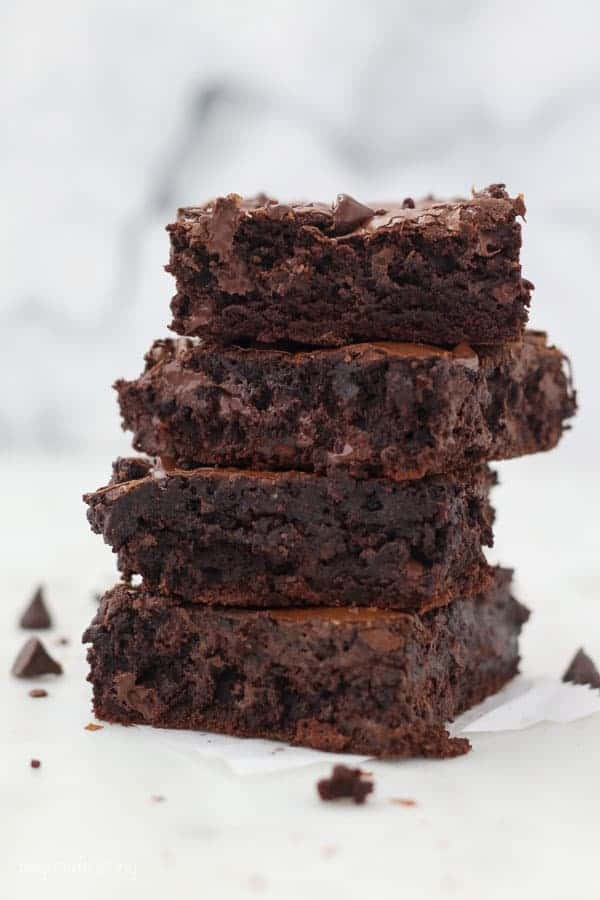 A stack of 4 thick fudgy brownies with melted chocolate chips