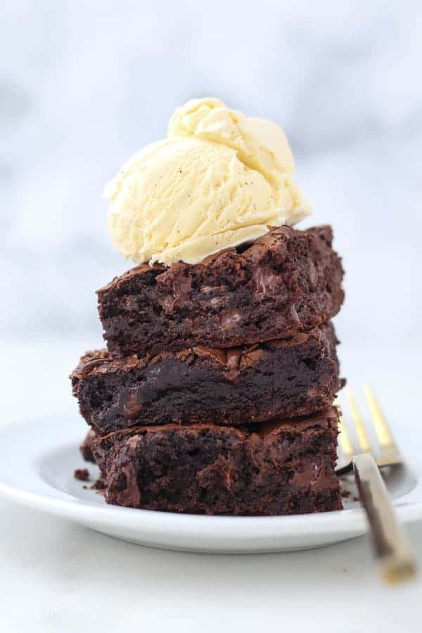 Three brownies on a white plate with a big scoop of vanilla ice cream on top and gold fork laying on the plate