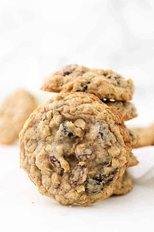 A stack of oatmeal raisin cookies and one big cookie is leaning up against the stack showing the raisins on top