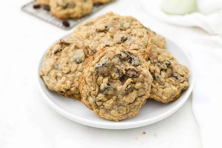 A wide angle shot of a white plate stacked with oatmeal raisin cookies