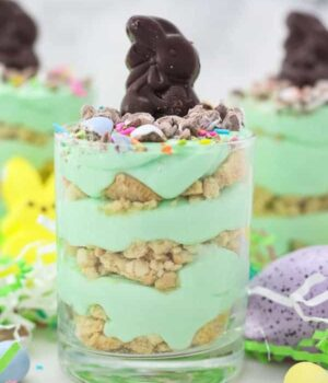 Three jars layered with Oreo and green colored mousse topped with an Easter bunny candy