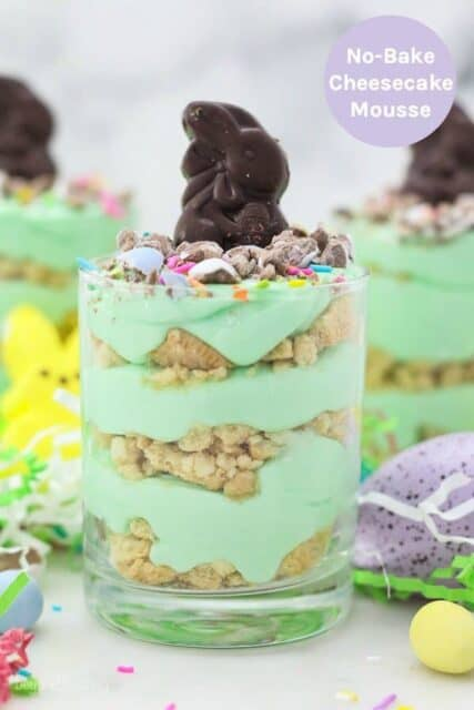 Three jars layered with Oreo and green colored mousse topped with an Easter bunny candy with a text overlay