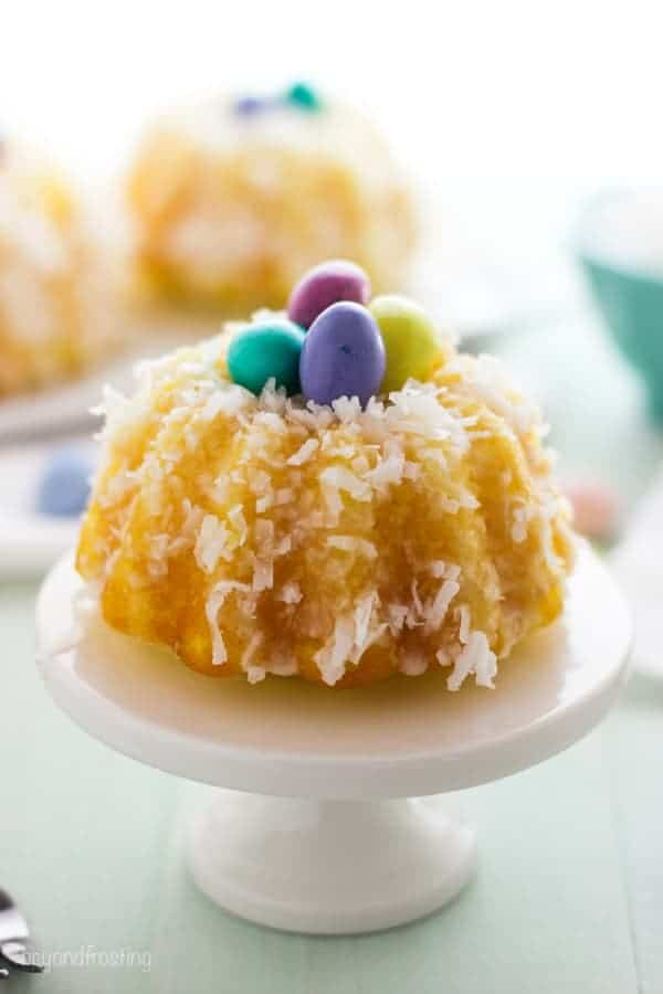 A small white cake stand holding a lemon bundt that that is covered in coconut and filled with mini chocolate eggs