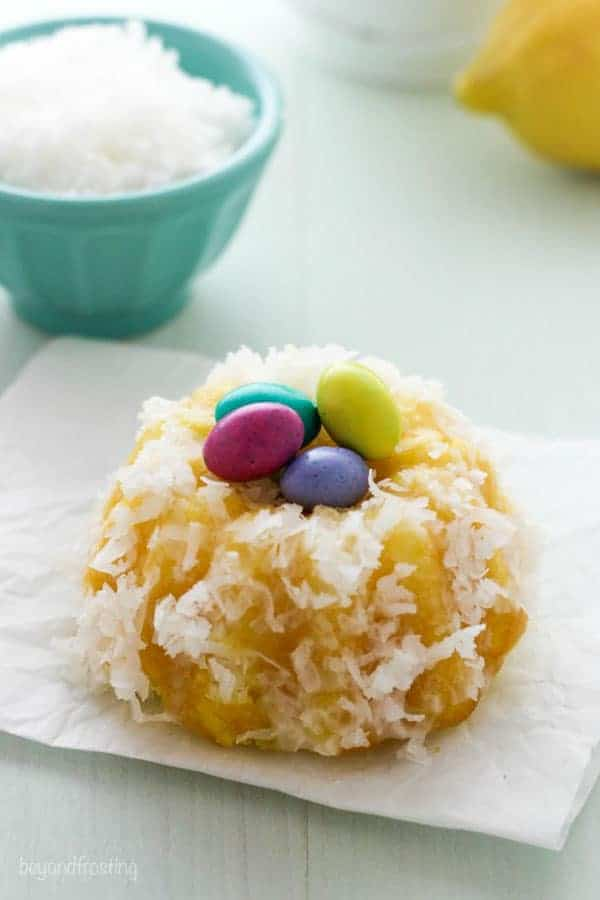 A mini bundt cake covered in coconut and 4 MnMs in the middle