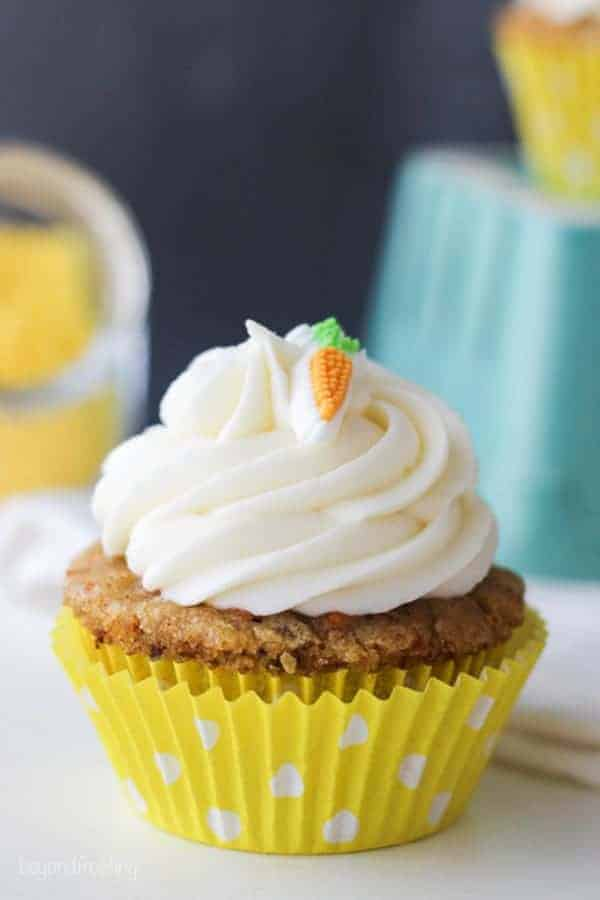 A perfect carrot cake cupcake in a yellow polka dot wrapper
