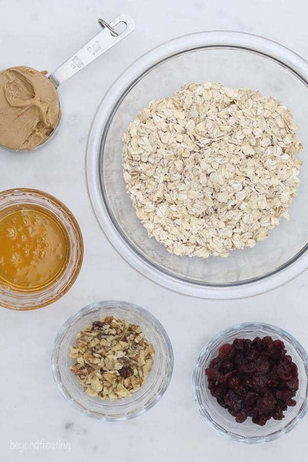 An overhead shot of glass bowls filled with rolled oats, honey, peanut butter, walnuts and cranberries