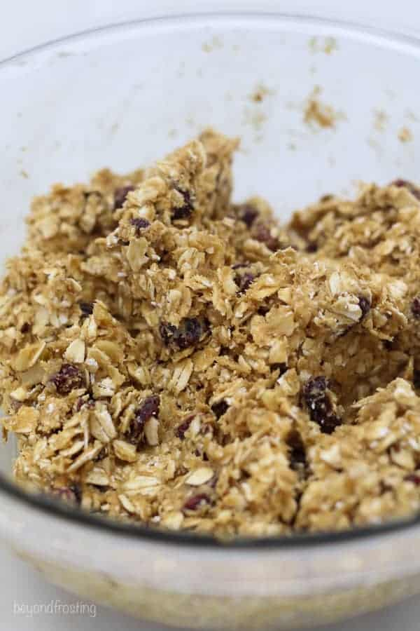 A close up shot of a glass bowl of ingredients such as rolled oats, cranberries and peanut butter