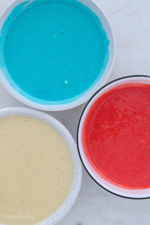 an overhead shot of 3 bowls of cake batter, a white one, a blue one and a red one