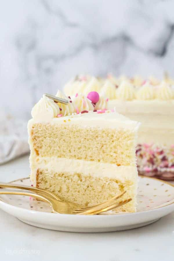 A slice of vanilla cake with pink sprinkles on a gold polka dot plate