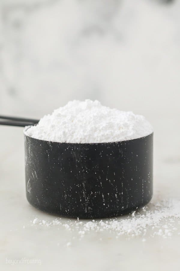 A black measuring cup filled with powdered sugar