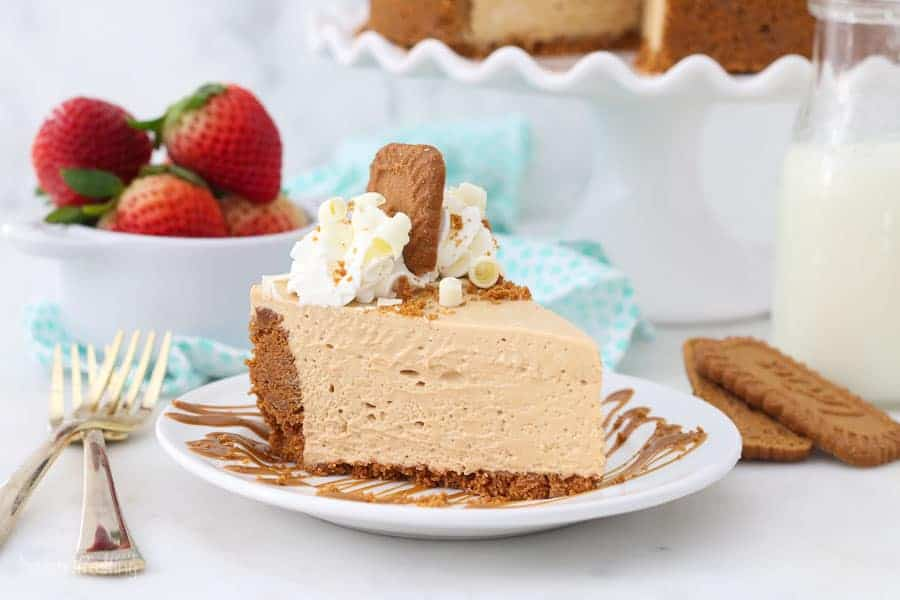 A slice of Biscoff pie on a white plate, a jar of strawberries in the background