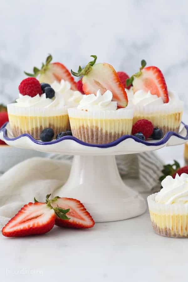 A white cake plate with mini cheesecake topped with Strawberries
