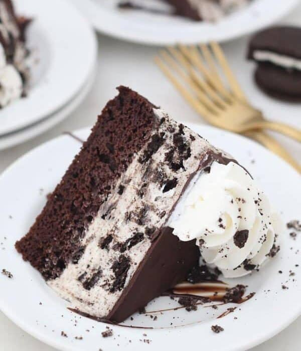 a slice of Oreo ice cream cake on a white plate- a layer of chocolate cake and a layer of oreo ice cream
