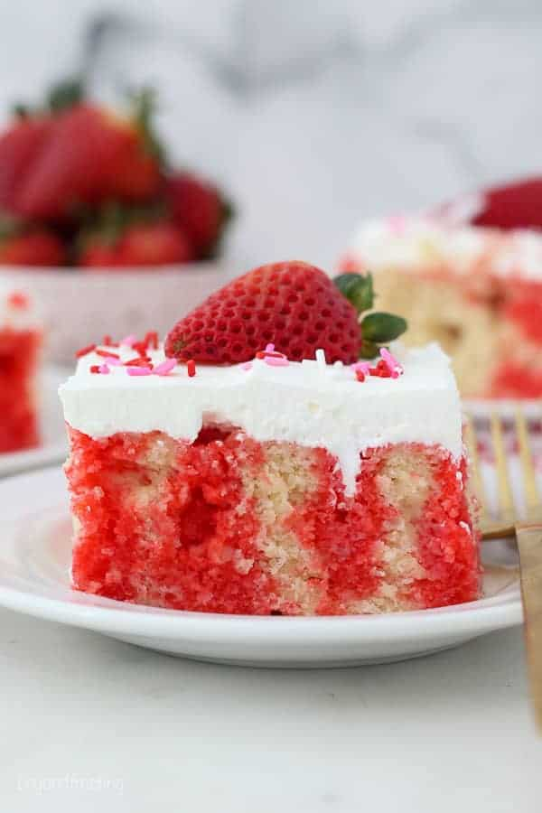A head on shot of a slice of poke cake, showing the red jello on the inside, garnished with a strawberry