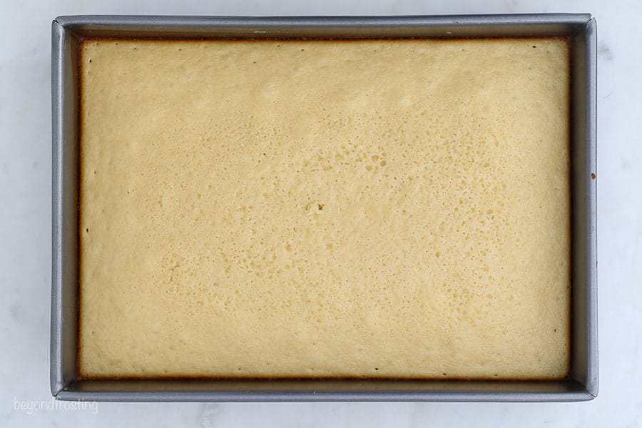 An overhead shot of a vanilla cake bake in a 9x13 inch pan