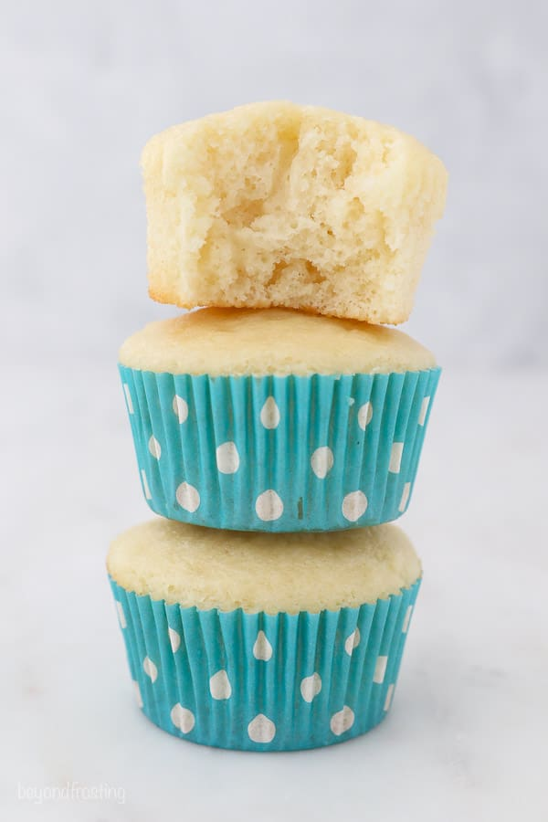 Three vanilla cupcakes stacked on top of one another, the top one has a bite taken out of it