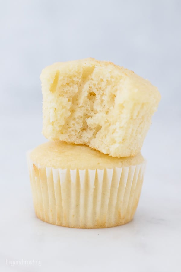 two vanilla cupcakes stacked on top of one another, the top one has a bite taken out of it