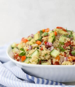 a white dish filled with quinoa and chopped vegetables and a blue stripe napkin