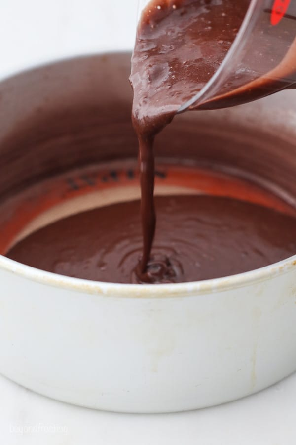 a measuring cup pouring chocolate cake batter into a cake pan