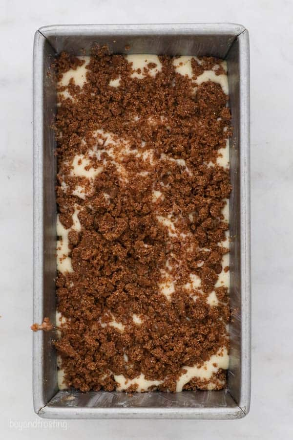 an overhead shot of a loaf pan filled with batter and topped with a cinnamon crumble