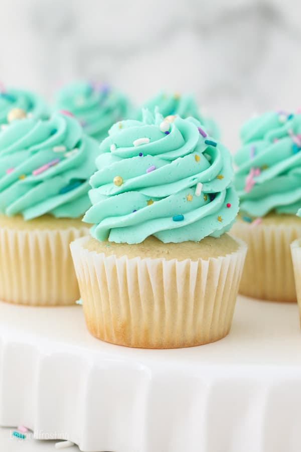 Vanilla cupcakes with teal frosting on a white cake plate