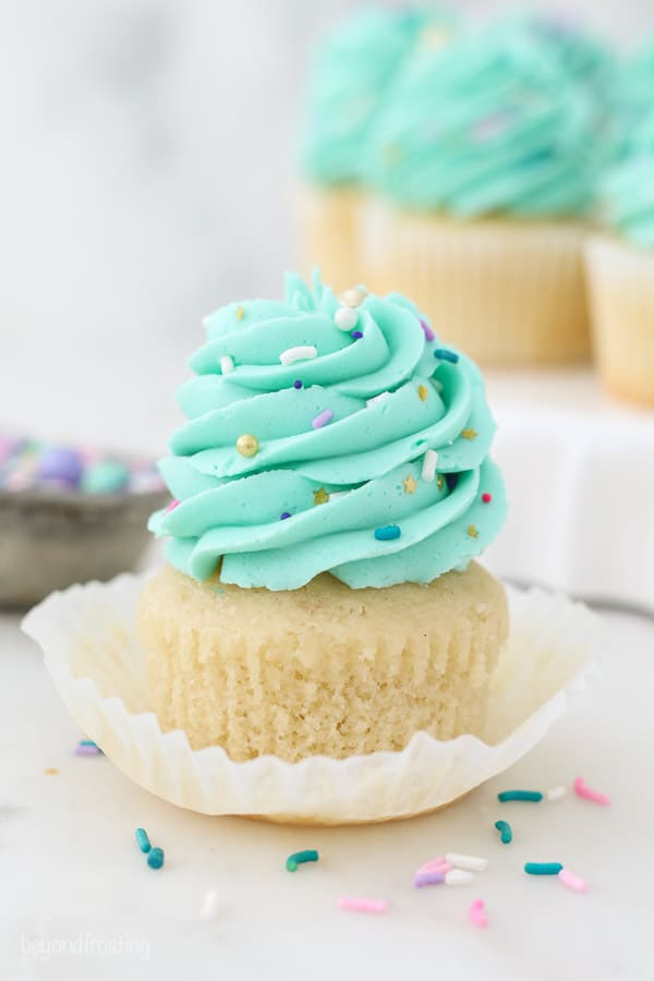 An unwrapped vanilla cupcake with teal frosting and sprinkles