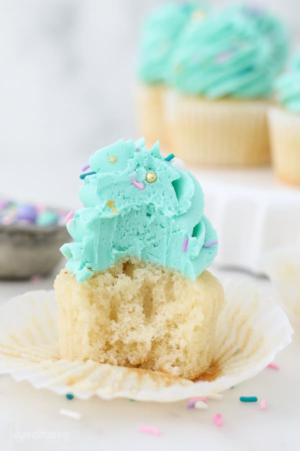 A cupcake with teal frosting has a bite taken out of it