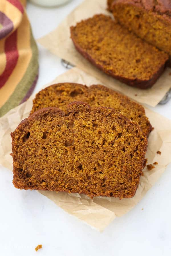 two slices of pumpkin bread on a piece of brown parchment paper