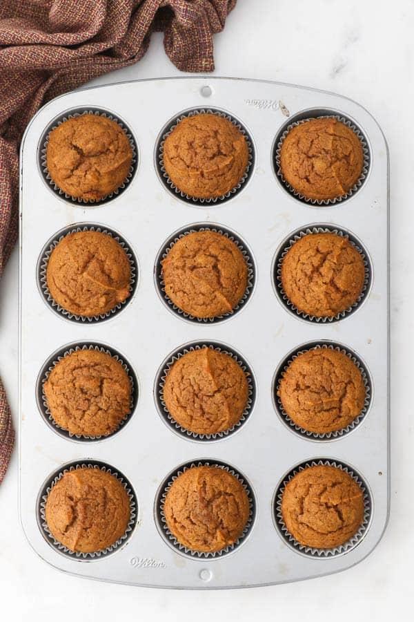 an overhead shot of 12 pumpkin muffins in a muffin pan