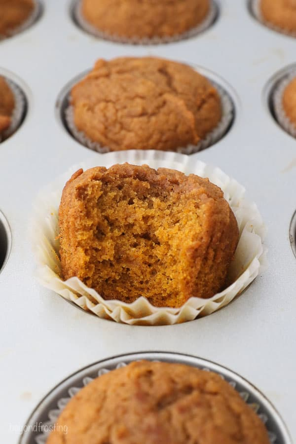 a muffins pan with pumpkin muffins, one has a bite missing