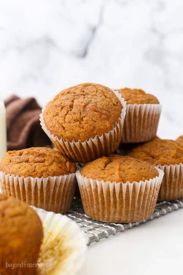 pumpkin muffins stacked on a wire cooling rack
