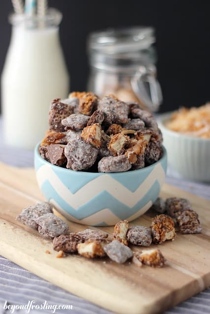 A Bowl of Samoa Muddy Buddies on a Cutting Board Beside a Glass of Milk
