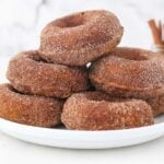 stacked cinnamon and sugar donuts on a white plate with cinnamon sticks in the background