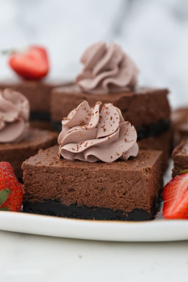 a serving plate with chocolate cheesecake bars topped with chocolate whipepd cream